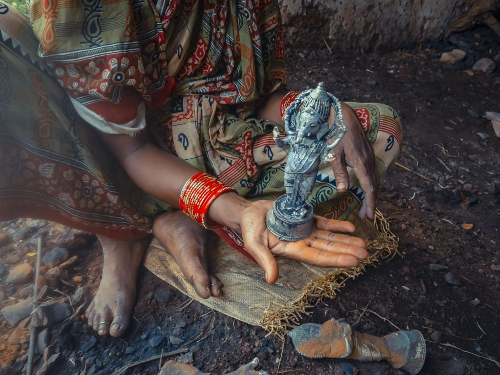 Artisan holding the finsihed Dhokra statue after cleaning
