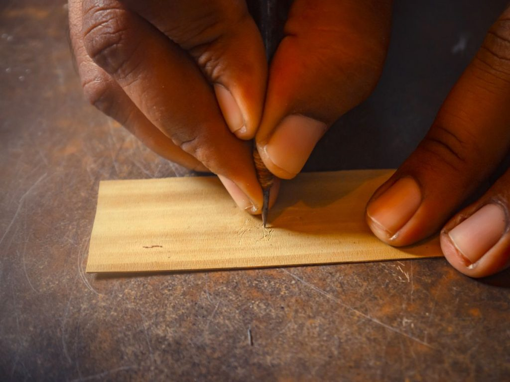 Artisan etching designs over the palm leaf using an iron stylus