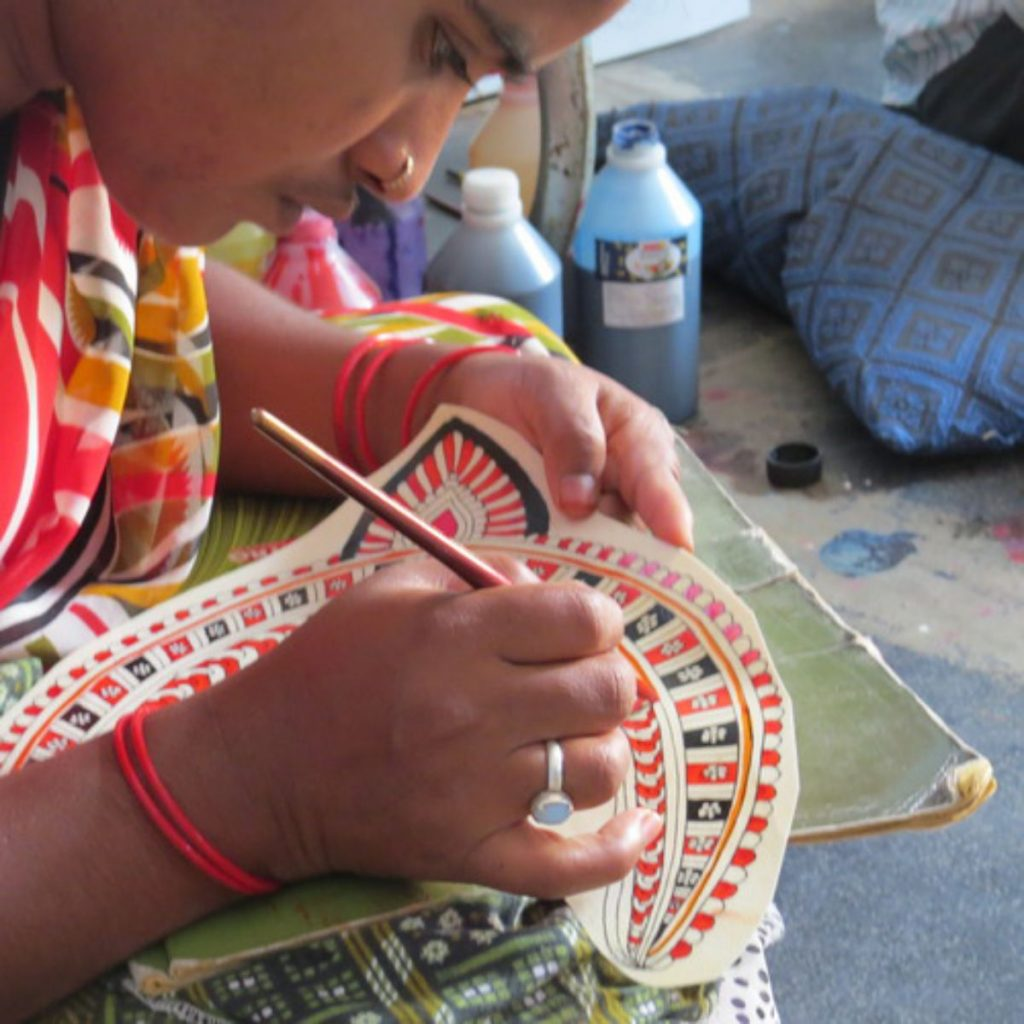An artisan painting on the proccesed goat hide for the jewellery