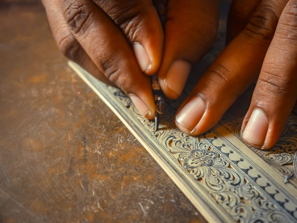 Artisan carving details over the palm leaf for pattachittra