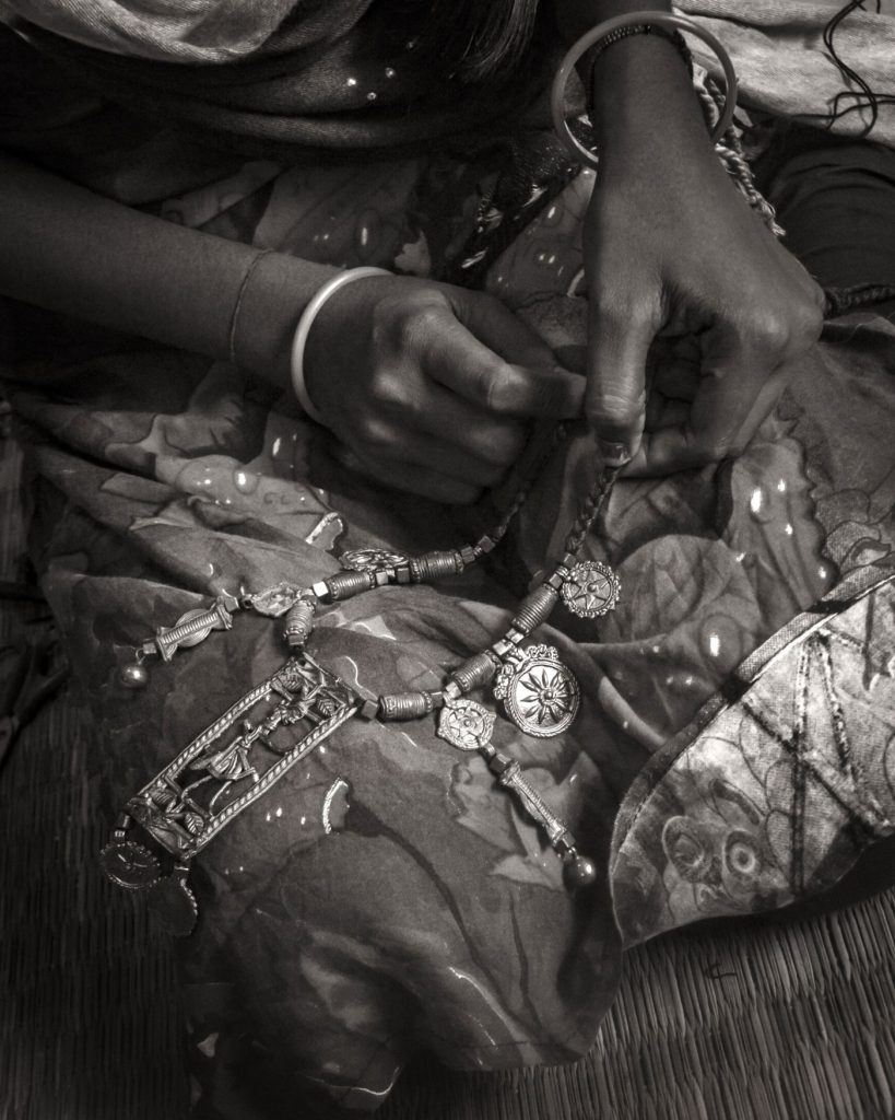 Artisan stringing Dhokra motifs into a necklace
